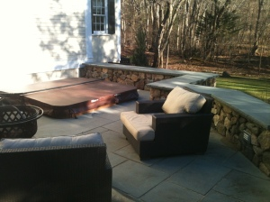 Stone deck, wall, and hot tub by Don Nyren Masonry in Wellesley, Massachusetts.